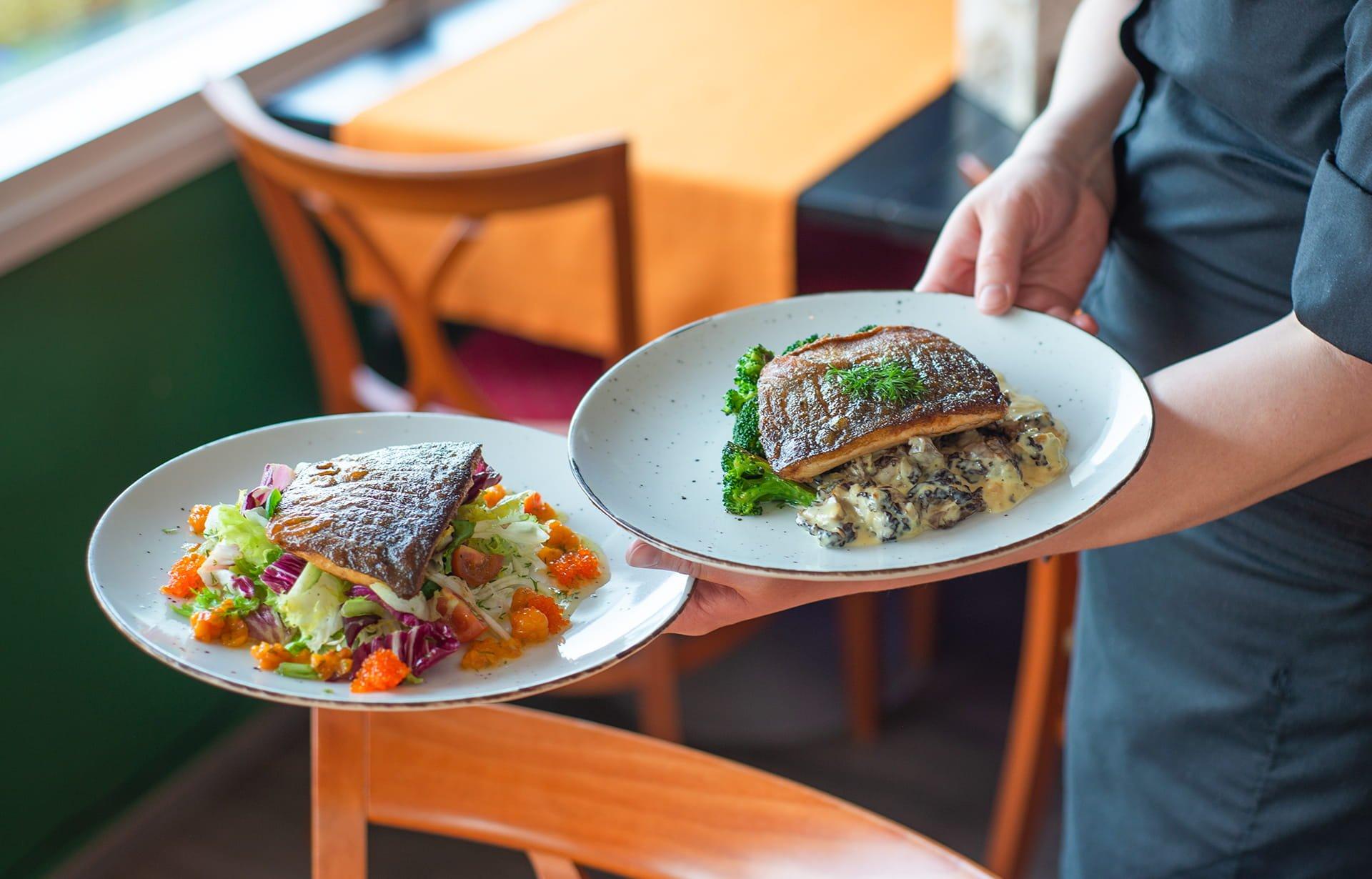 Tarjoilija kantaa kahta kala-annosta pöytään.
